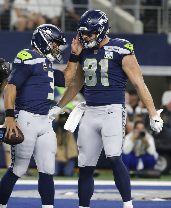 Seattle Seahawks quarterback Russell Wilson (3) and tight end Nick Vannett (81) celebrate a touchdown scored on a running play by Wilson during the second half of the NFC wild-card NFL football game agains the Dallas Cowboys, in Arlington, Texas, Saturday, Jan. (AP Photo/Michael Ainsworth)