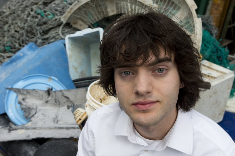 FILE - In this May 11, 2017, file photo, Dutch innovator Boyan Slat poses for a portrait next to a pile of plastic garbage prior to a press conference in Utrecht, Netherlands. (600-meter) long floating boom will be towed to Hawaii. If it can't be repaired there it will be loaded on a barge and returned to its home port of Alameda, California. The boom broke apart under constant wind and waves. Slat says he's disappointed, but not discouraged. (AP Photo/Peter Dejong, File)