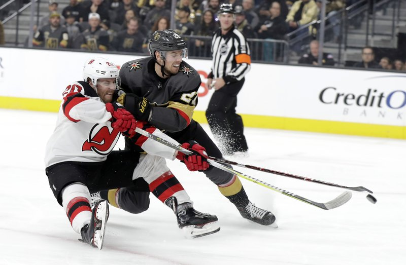 New Jersey Devils center Blake Coleman (20) shoots while covered by Vegas Golden Knights defenseman Shea Theodore during the first period of an NHL hockey game Sunday, Jan. (AP Photo/Isaac Brekken)