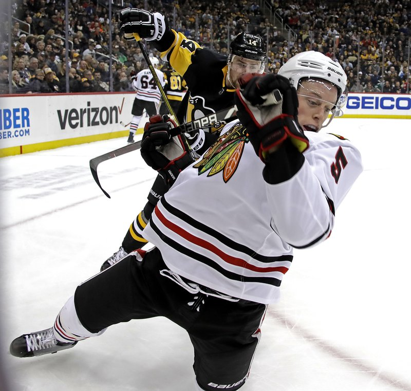 Chicago Blackhawks' Connor Murphy (5) is tripped by Pittsburgh Penguins' Tanner Pearson (14) during the second period of an NHL hockey game in Pittsburgh, Sunday, Jan. (AP Photo/Gene J. Puskar)