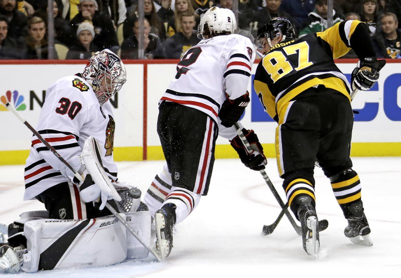Chicago Blackhawks goaltender Cam Ward (30) stops a shot by Pittsburgh Penguins' Sidney Crosby (87) with Duncan Keith (2) defending during the second period of an NHL hockey game in Pittsburgh, Sunday, Jan. (AP Photo/Gene J. Puskar)