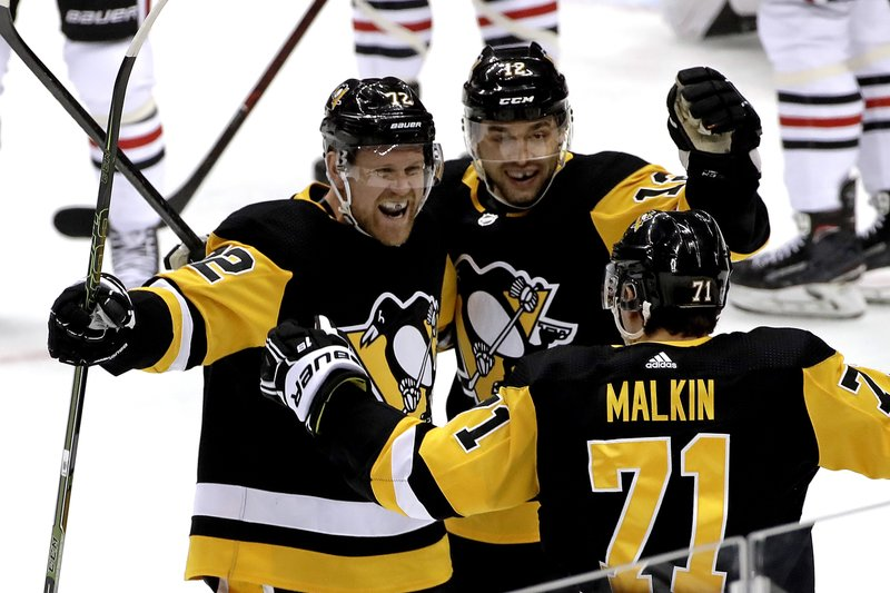Pittsburgh Penguins' Patric Hornqvist (72) celebrates his goal with Dominik Simon (12) and Evgeni Malkin (71) during the first period of an NHL hockey game against the Chicago Blackhawks in Pittsburgh, Sunday, Jan. (AP Photo/Gene J. Puskar)