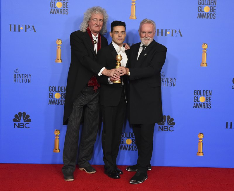 Brian May, left, and Roger Taylor, right, of Queen, and Rami Malek pose in the press room with the award for best motion picture, drama for