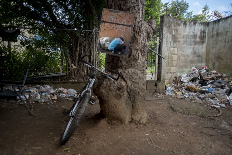 In this Dec. 14, 2018 photo, a mirror tied to a tree reflects a heroin addict preparing his dose, in an area popular with users behind an abandoned home in Humacao, Puerto Rico. (AP Photo/Carlos Giusti)