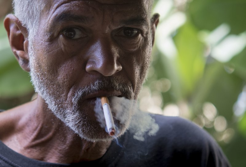 In this Dec. 14, 2018 photo, Wilfredo Rivera smokes a cigarette after injecting heroin, in an area popular with users behind an abandoned home in Humacao, Puerto Rico. (AP Photo/Carlos Giusti)