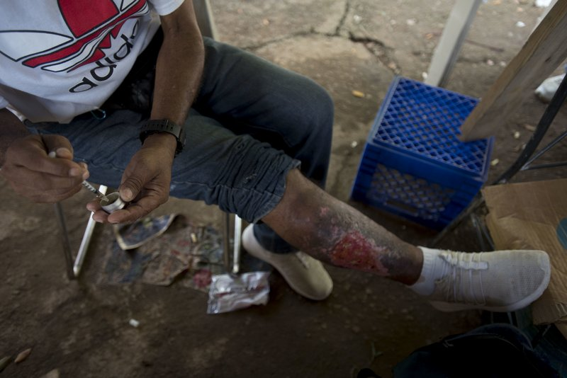 In this Dec. 14, 2018 photo, a man fills his syringe with heroin in an area popular with users behind an abandoned home in Humacao, Puerto Rico. (AP Photo/Carlos Giusti)