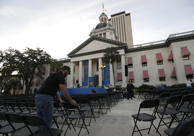 A worker arranges chairs outside of the Capitol building in preparation for the inauguration of Florida Gov. (AP Photo/Lynne Sladky)