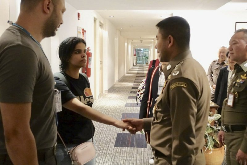 In this photo released by the Immigration Police,  Saudi woman Rahaf Mohammed Alqunun, second left, shakes hand with Chief of Immigration Police Maj. (Immigration police via AP)