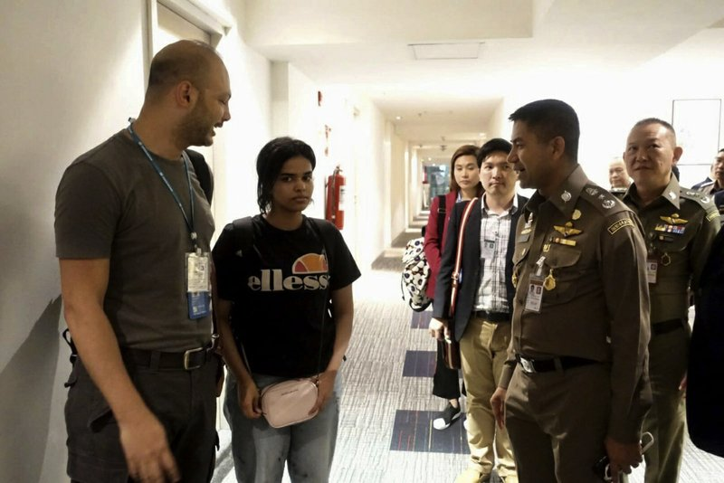 In this photo released by the Immigration Police, Chief of Immigration Police Maj. Gen. Surachate Hakparn, right talks to Saudi woman Rahaf Mohammed Alqunun,second left, before leaving the Suvarnabhumi Airport in Bangkok Monday, Jan. (Immigration police via AP)