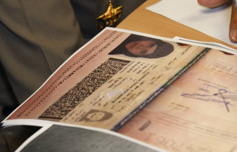 A passport copy of Rahaf Mohammed Alqunun sits on the desk as Chief of Immigration Police Maj. Gen. Surachate Hakparn talks to media about her status during a press conference at the Suvarnabhumi Airport in Bangkok Monday, Jan. (AP Photo/Sakchai Lalit)