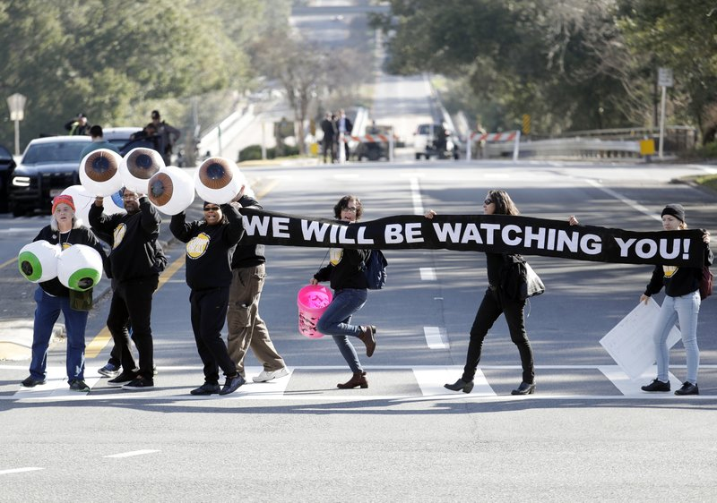 Protestors march past the Capitol before former U.S. Rep. Ron DeSantis is sworn in as Florida's new governor, Tuesday, Jan. (AP Photo/Lynne Sladky)