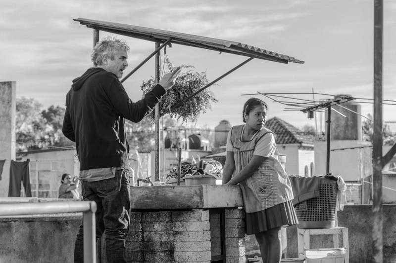 This image released by Netflix shows filmmaker Alfonso Cuaron, left, and actress Yalitza Aparicio on the set of
