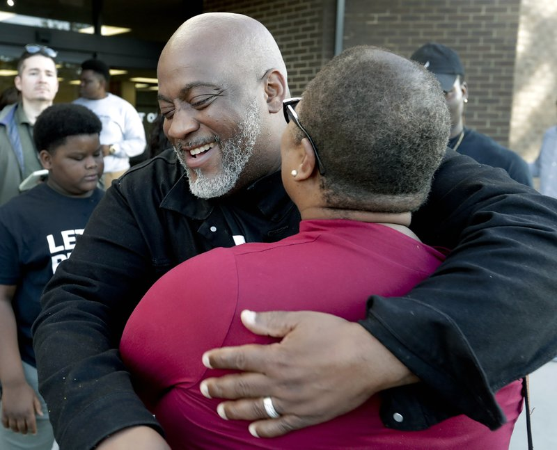 Former felon Desmond Meade and president of the Florida Rights Restoration Coalition, left, hugs Melanie Campbell with the National Coalition Black Civic Participation, after registering to vote at the Supervisor of Elections office Tuesday, Jan. (AP Photo/John Raoux)