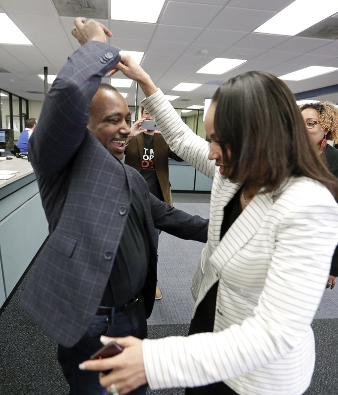 State Attorney Aramis Ayala, right, celebrates with her husband David, a former felon, after he registered to vote at the Supervisor of Elections office Tuesday, Jan. (AP Photo/John Raoux)