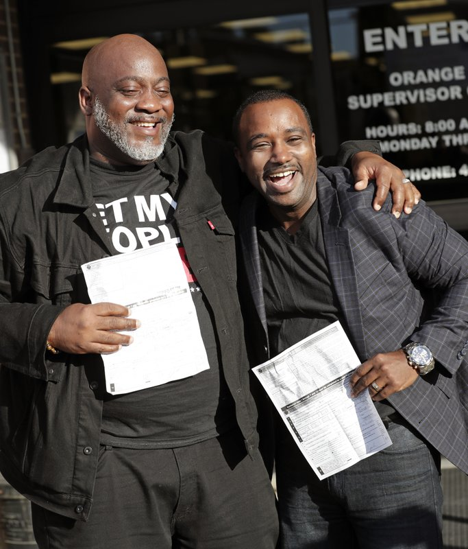 Former felons Desmond Meade, president of the Florida Rights Restoration Coalition, left, and David Ayala, husband of State Attorney Aramis Ayala, celebrate with copies of their voter registration forms after they registered at the Supervisor of Elections office Tuesday, Jan. (AP Photo/John Raoux)