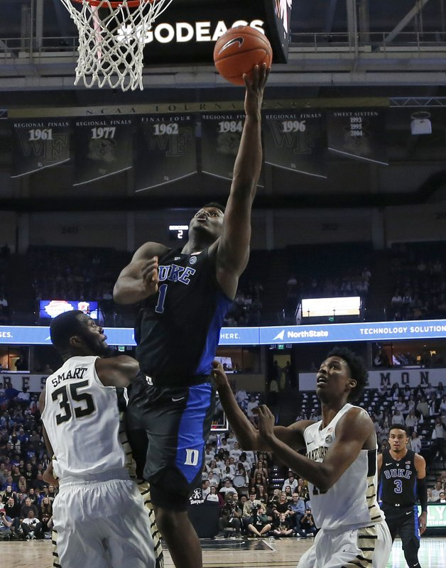 Duke's Zion Williamson (1) drives between Wake Forest's Ikenna Smart (35) and Jaylen Hoard during the first half of an NCAA college basketball game in Winston-Salem, N. (AP Photo/Chuck Burton)