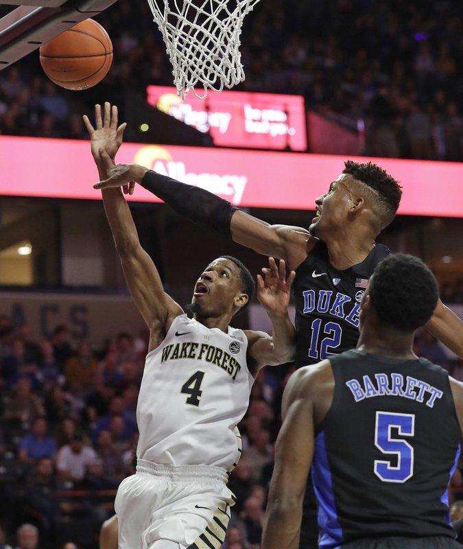 Duke's Javin DeLaurier (12) blocks a shot by Wake Forest's Torry Johnson (4) during the first half of an NCAA college basketball game in Winston-Salem, N. (AP Photo/Chuck Burton)