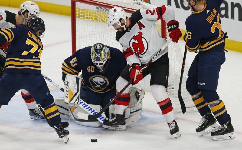 Buffalo Sabres goalie Carter Hutton (40) stops New Jersey Devils forward Kyle Palmieri (21) during the second period of an NHL hockey game, Tuesday, Jan. (AP Photo/Jeffrey T. Barnes)