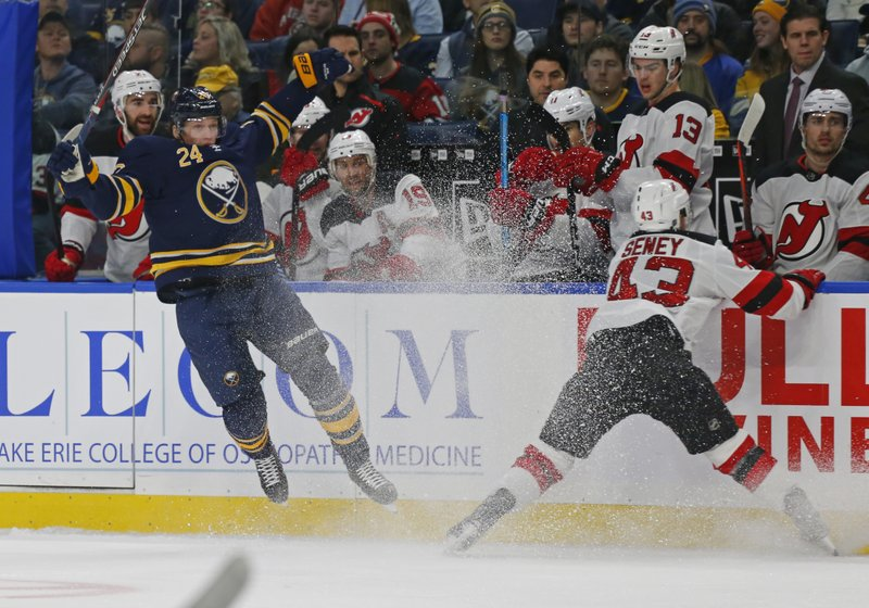 Buffalo Sabres defenseman Lawrence Pilut (24) and New Jersey Devils forward Brett Seney (43) collide during the first period of an NHL hockey game, Tuesday, Jan. (AP Photo/Jeffrey T. Barnes)