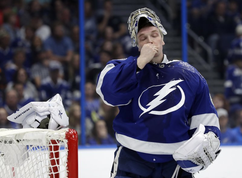 Tampa Bay Lightning goaltender Andrei Vasilevskiy (88) wipes his face after getting covered with ice by Columbus Blue Jackets center Brandon Dubinsky during the first period of an NHL hockey game Tuesday, Jan. (AP Photo/Chris O'Meara)