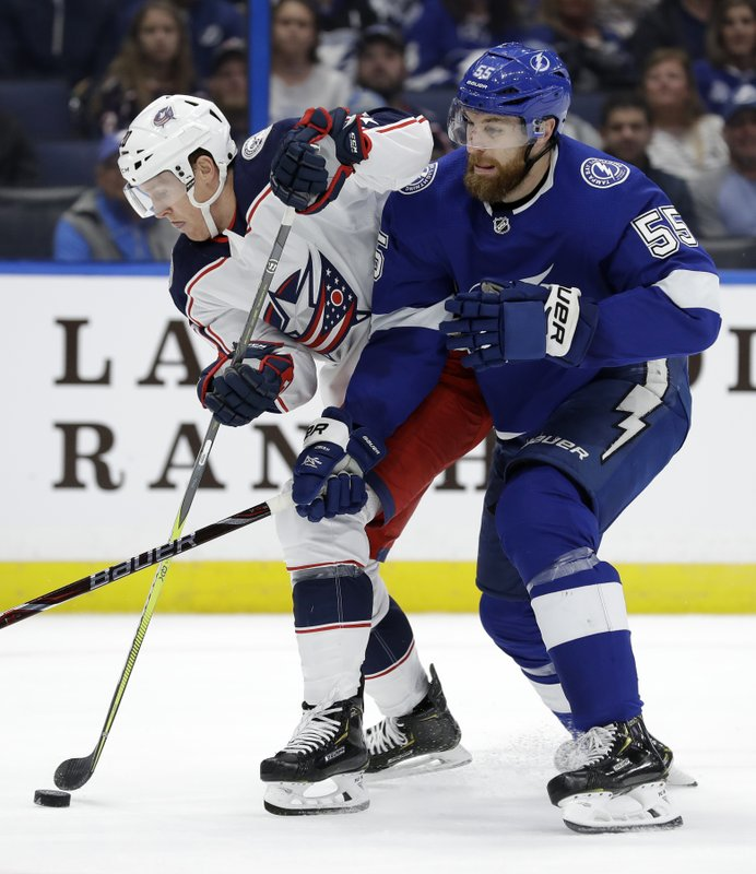 Tampa Bay Lightning defenseman Braydon Coburn (55) tries to check Columbus Blue Jackets center Riley Nash (20) off the puck during the first period of an NHL hockey game Tuesday, Jan. (AP Photo/Chris O'Meara)