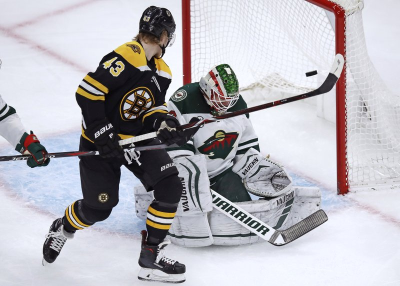 Boston Bruins center Danton Heinen (43) tips the puck past Minnesota Wild goaltender Alex Stalock, right, for a goal during the first period of an NHL hockey game in Boston, Tuesday, Jan. (AP Photo/Charles Krupa)