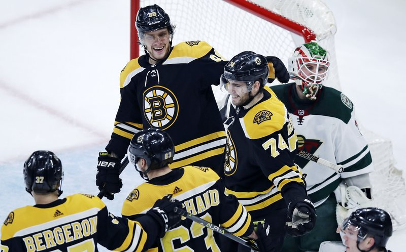 Boston Bruins left wing Jake DeBrusk (74) smiles as he is congratulated by teammates after deflecting a shot by Patrice Bergeron off his chest for a goal, beating Minnesota Wild goaltender Alex Stalock, right, during the first period of an NHL hockey game in Boston, Tuesday, Jan. (AP Photo/Charles Krupa)