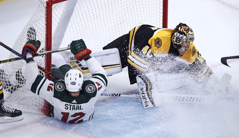 Boston Bruins goaltender Tuukka Rask, right, makes a save as Minnesota Wild center Eric Staal (12) slips into the net during the first period of an NHL hockey game in Boston, Tuesday, Jan. (AP Photo/Charles Krupa)