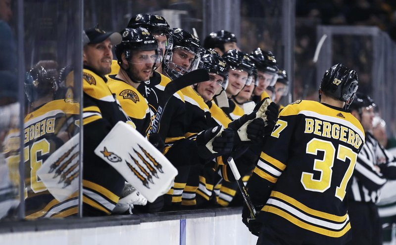Boston Bruins center Patrice Bergeron (37) is congratulated by teammates after his goal against the Minnesota Wild during the second period of an NHL hockey game in Boston, Tuesday, Jan. (AP Photo/Charles Krupa)