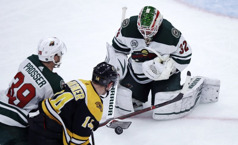 Minnesota Wild goaltender Alex Stalock (32) makes a stick save as Boston Bruins right wing Chris Wagner (14) looks for the rebound during the third period of an NHL hockey game in Boston, Tuesday, Jan. (39). (AP Photo/Charles Krupa)