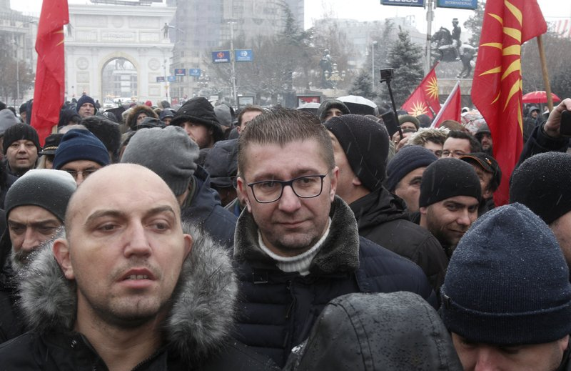 Hristijan Mickoski, center, leader of the opposition VMRO-DPMNE party, arrives to a protest against the change of the country's constitutional name, outside the parliament building prior a session of the Macedonian Parliament in the capital Skopje, Wednesday, Jan. (AP Photo/Boris Grdanoski)