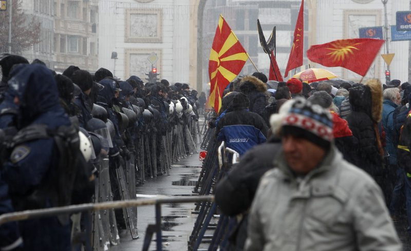 Police stand guard during a protest against the change of the country's name outside the parliament building in Skopje, Macedonia, Wednesday, Jan. (AP Photo/Boris Grdanoski)