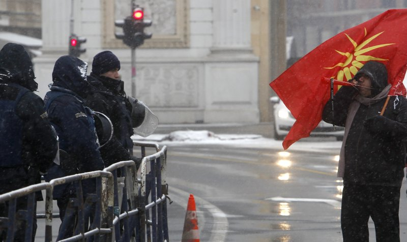 A protestor blows a horn, standing next to a police cordon during a protest against the change of the country's name outside the parliament building in Skopje, Macedonia, Wednesday, Jan. (AP Photo/Boris Grdanoski)