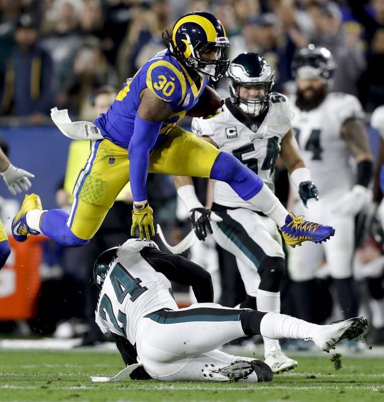 FILE - In this Dec. 16, 2018, file photo, Los Angeles Rams running back Todd Gurley runs over Philadelphia Eagles free safety Corey Graham during the first half in an NFL football game, in Los Angeles. (AP Photo/Marcio Jose Sanchez, File)