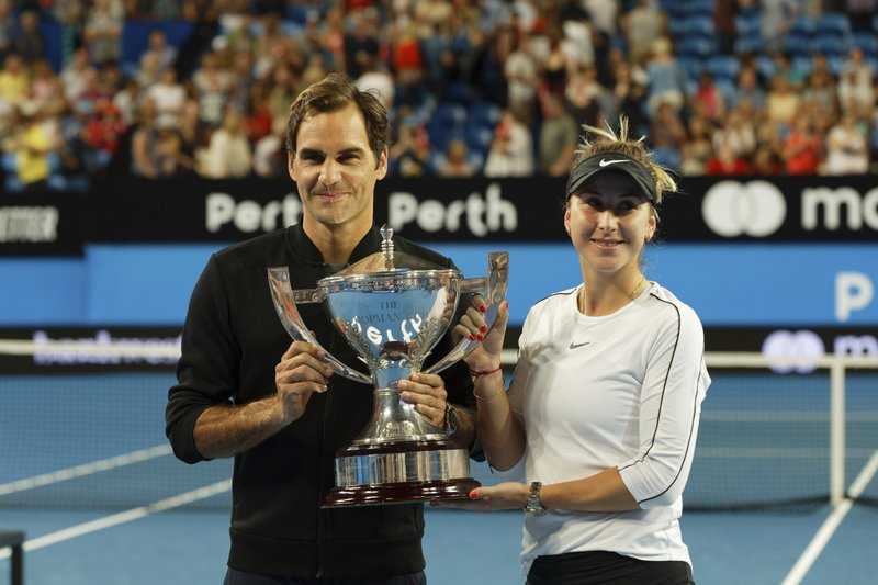 Switzerland's Roger Federer and Belinda Bencic hold the trophy after winning the final against Alexander Zverev and Angelique Kerber of Germany at the Hopman Cup in Perth, Australia, Saturday Jan. (AP Photo/Trevor Collens)
