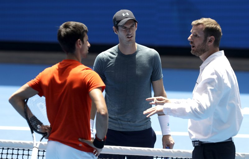 Match umpire Simon Canavan, right, talks with Britain's Andy Murray, centre, and Serbia's Naval Djokovic ahead of their practice match at the Australian Open tennis championships in Melbourne, Australia, Thursday, Jan. (AP Photo/Mark Baker)