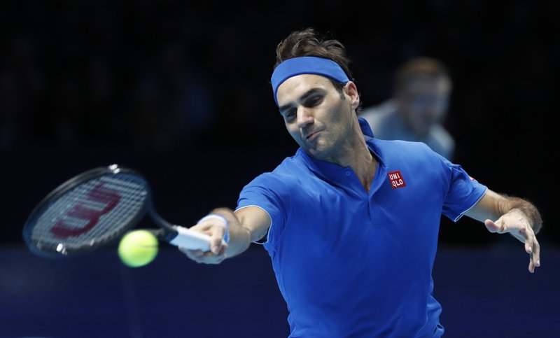 FILE - In this Nov. 13, 2018, file photo, Roger Federer of Switzerland plays a return to Dominic Thiem of Austria during their ATP World Tour Finals men's singles tennis match at O2 arena in London. (AP Photo/Alastair Grant, File)
