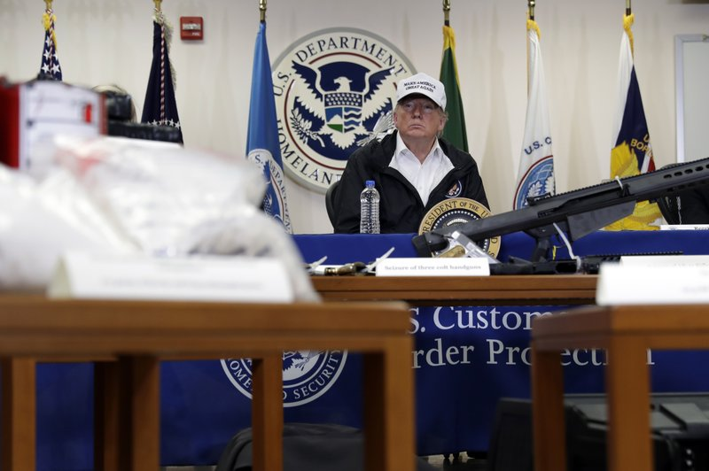 With illegal drugs and weapons displayed in the foreground, President Donald Trump speaks at a roundtable on immigration and border security at U. (AP Photo/ Evan Vucci)