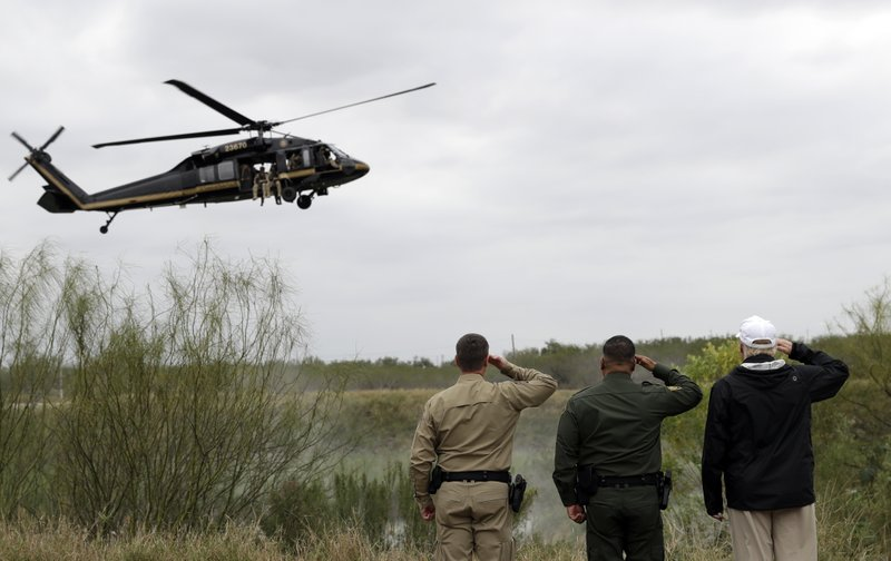 President Donald Trump salutes as a U.S. customs and Border Protection helicopter passes as he tours the U. (AP Photo/ Evan Vucci)