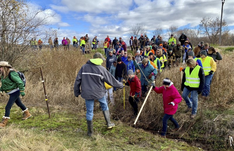 FILE - In this Oct. 23, 2018, file photo, volunteers cross a creek and barbed wire near Barron, Wis., on their way to a ground search for 13-year-old Jayme Closs who was discovered missing Oct. (AP Photo/Jeff Baenen, File)