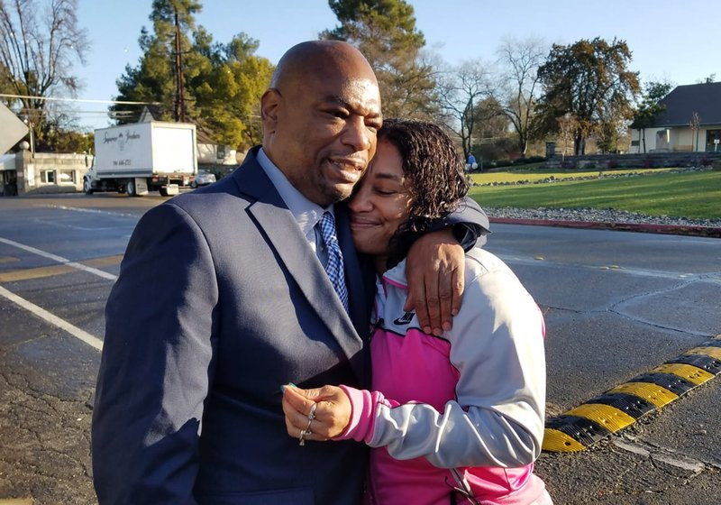 This photo released by the California Innocence Project shows Quintin Morris, 53, embracing his sister Billie Sullivan after he was released from Folsom Prison after spending 27 years behind bars for attempted murders he denied committing, outside the prison in Folsom, Calif. (Alissa Bjerkhoel/California Innocence Project via AP)