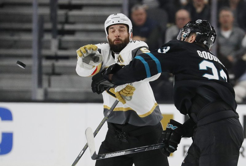 San Jose Sharks right wing Barclay Goodrow, right, and Vegas Golden Knights defenseman Deryk Engelland try to knock the puck out of the air during the second period of an NHL hockey game Thursday, Jan. (AP Photo/John Locher)
