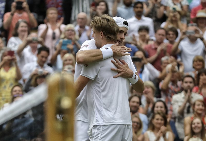 FILE - In this July 13, 2018, file photo, South Africa's Kevin Anderson hugs John Isner of the United States, right, after defeating him in their men's singles semifinals match at the Wimbledon Tennis Championships, in London. (AP Photo/Kirsty Wigglesworth, File)