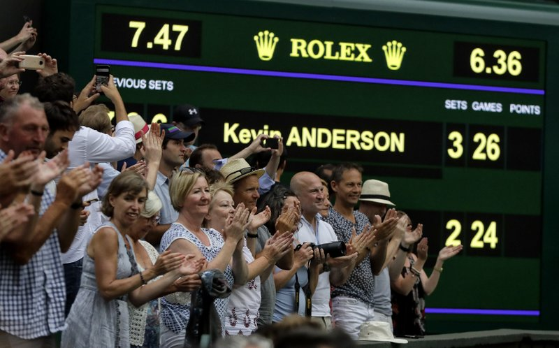FILE - In this July 13, 2018, file photo, spectators applaud as the scoreboard displays the final score in the men's singles semifinals match in which John Isner of the United States was defeated by South Africa's Kevin Anderson, at the Wimbledon Tennis Championships, in London. (AP Photo/Kirsty Wigglesworth, File)
