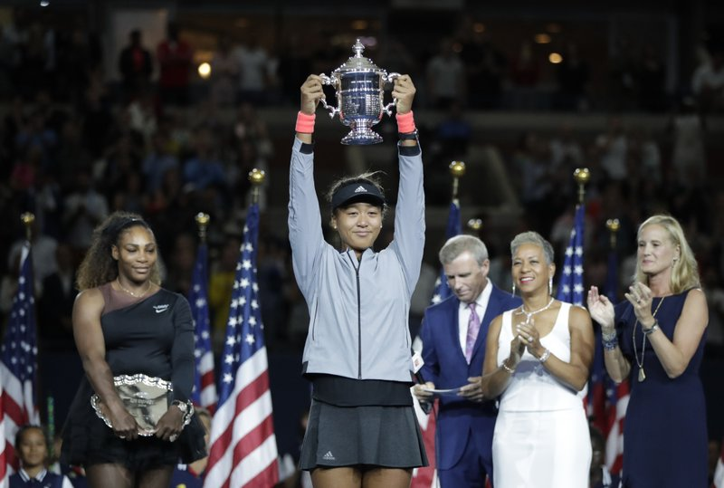 FILE - In this Sept. 8, 2018, file photo, Naomi Osaka, of Japan, holds the trophy after defeating Serena Williams in the women's final of the U. (AP Photo/Julio Cortez, File)