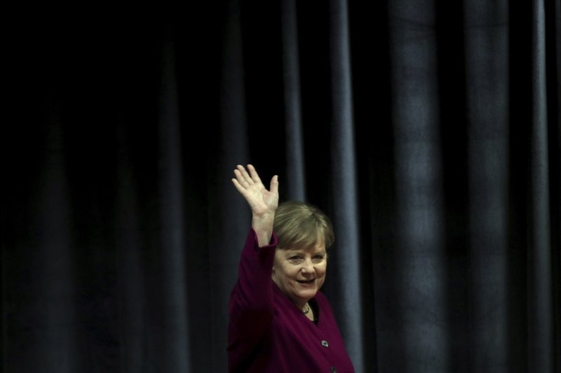 German Chancellor Angela Merkel waves the students during her visit in a German school in Athens, Friday, Jan. (AP Photo/Petros Giannakouris)