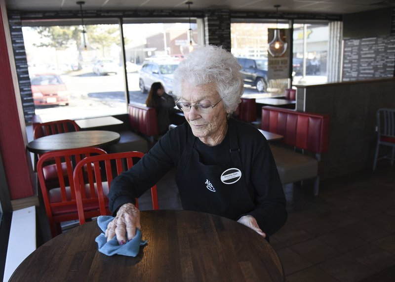 Making the rounds to clean up table tops, after 25 years at Arby's Millcreek, Utah, 94-year-old Dorothy Bale has no plans to retire from the job she started when she was 69. (Francisco Kjolseth/The Salt Lake Tribune via AP)