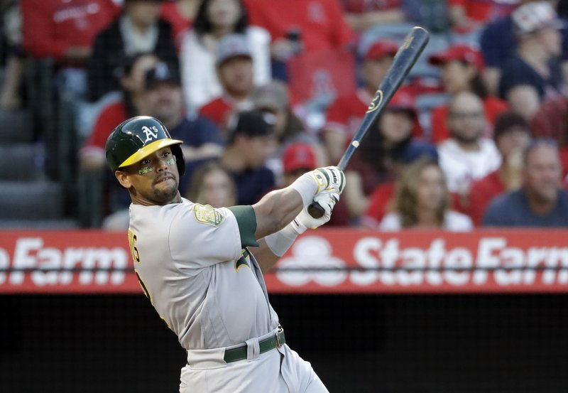 FILE - In this Sept. 29, 2018 file photo Oakland Athletics' Khris Davis follows through on his two-run home run against the Los Angeles Angels during the first inning of a baseball game, in Anaheim, Calif. (AP Photo/Marcio Jose Sanchez, File)