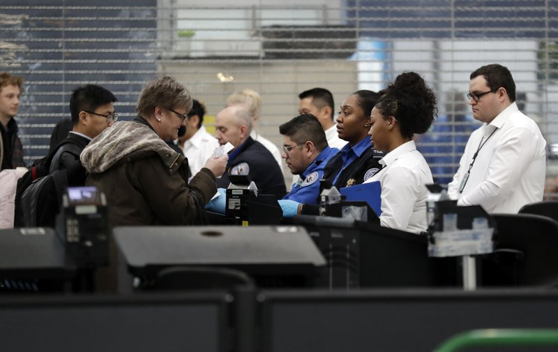 Transportation Security Administration officers work at a checkpoint at O'Hare airport in Chicago, Friday, Jan. (AP Photo/Nam Y. Huh)