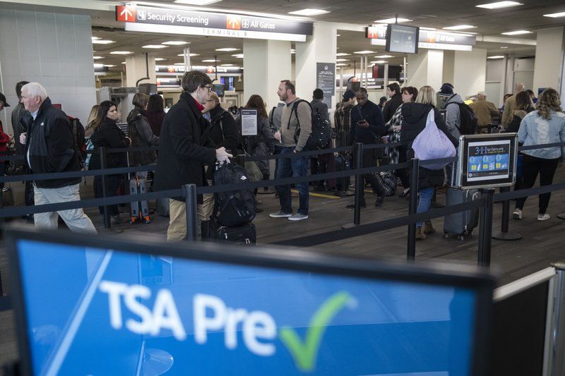 Passengers wait in line at a Transportation Security Administration checkpoint at the Philadelphia International Airport in Philadelphia, Friday, Jan. (AP Photo/Matt Rourke)